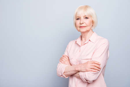 Old blonde lady smiling with folded hands on grey background Фото со стока
