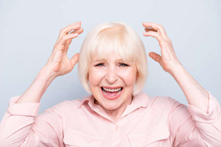 Portrait of old adult lady shocked devastated facial expression, opened mouth, raising palms to head, on grey background, isolated