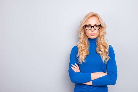 Portrait with copy space, empty place of pretty, trendy, charming, nice, sexy, cute, concentrated, clever woman in blue turtleneck, glasses having her arms crossed looking at camera