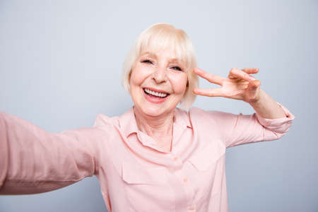 Portrait of old adult blonde glad cheerful caucasian lady smiling, photographing, making selfie on camera over grey background, showing v-sign victory peace gesture, isolated Stock Photo