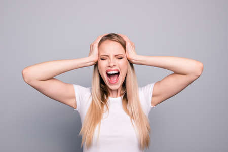Portrait of young blonde attractive gorgeous caucasian charming girl overreacting screaming loudly touching head with hands. Isolated over grey background