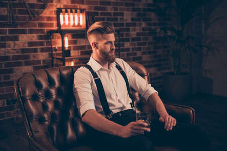 Portrait of stunning serious confident handsome thinking pondering pensive focused concentrated relaxed dreamy planning entrepreneur sitting on leather divan enjoying alcohol beverage in hands