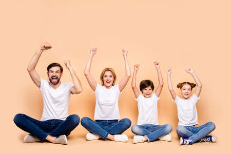 Young smiling family, bearded father, blonde mother, little boy and girl wearing blue jeans and white T-shirts, sitting in odrer of hierarchy in lotus pose raising up hands Stock Photo