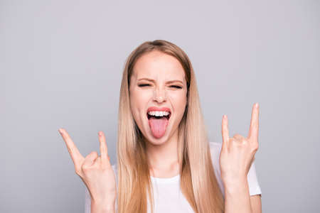 Portrait of young attractive girl wearing casual white t-shirt showing rock-n-roll sign double horns. Isolated over grey background Foto de archivo