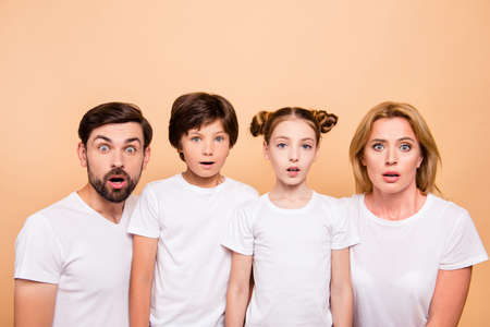 Closeup portrait of young family, bearded father, blonde mother and their little children, boy and girl, wearing white T-shirts showing surprising on camera on beige background Stock Photo
