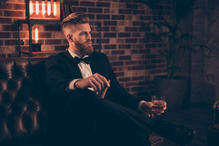 Posh chic wealthy lifestyle concept. Profile side-view portrait of serious thinking focused concentrated pensive stylish trendy rich arrogant freelancer chief sharp-dressed holding cigar beverage Standard-Bild