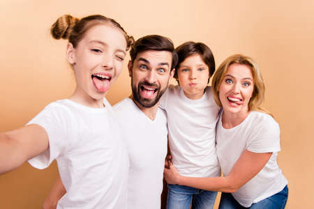 Self portrait of young attractive adorable beautiful smiling family, bearded father, blonde mother and their little children, boy and girl, wearing white T-shirts, showing their tongues