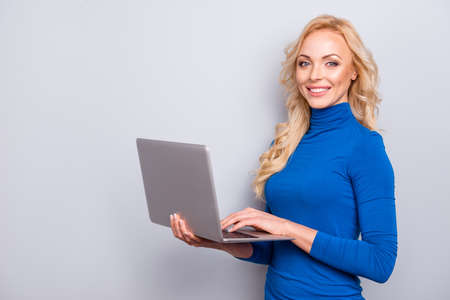 Portrait with copy space, empty place of pretty, trendy, charming, sexy, cute,  woman in blue turtleneck, looking at camera isolated on grey background, having laptop in hands, using wi-fi internet