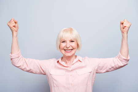 Portrait of old excited strong healthy lady raising hands up, smiling laughing, looking straight over grey background, isolated