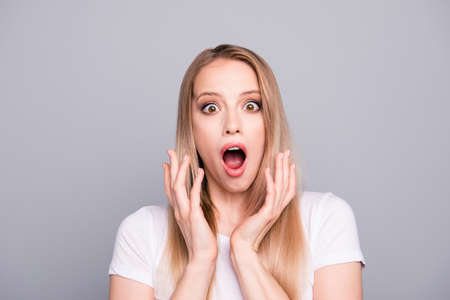 Portrait of young blonde gorgeous stunned shocked girl showing wow gesture. Isolated over grey background