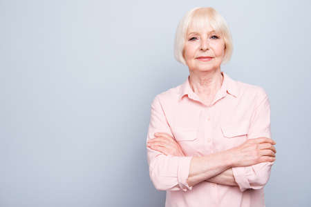 Old blonde lady smiling with folded hands on grey background standing straight, copy space Stock fotó