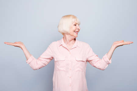 Old adult blonde glad cheerful lady smiling, showing gesture with hands, palms two sides, over grey background, looking left, isolated
