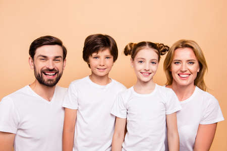 Closeup portrait of adorable attractive beautiful young family, bearded father, blonde mother and their little children, boy and girl, wearing white T-shirts smiling on camera on beige background