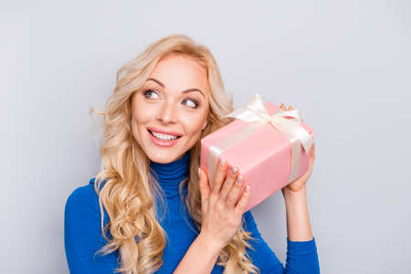 Portrait of pretty, trendy, charming, nice, sexy, cute woman in blue roll neck isolated on grey background holding present box in pink package with white bow near ear, trying to know what inside