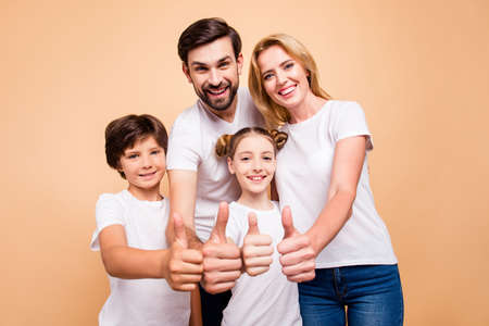 Portrait of young beautiful family, bearded father, blonde mother and their little children, boy and girl, wearing blue jeans and white T-shirts, showing thumbs up and smiling on beige background