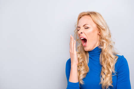 Portrait with copy space, empty place of pretty, trendy, charming, sexy, tired, cute, woman in blue turtleneck cover her wide open mouth with palm, having close eyes, very tired want to sleep