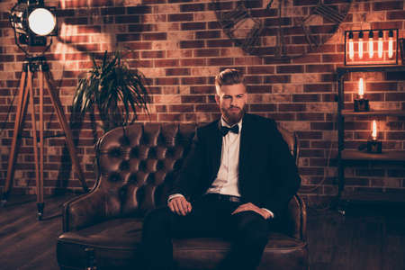 Portrait of well-off confident serious dream dreamy pensive planning handsome smart sharp-dressed wealthy freelancer having a rest relaxing enjoying atmosphere semi-lit room sitting on leather divan Stock Photo