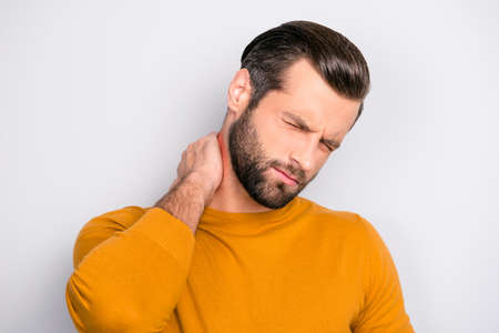Casual bright pullover people person pressure osteohondrosis concept. Close up portrait of upset stressed  freelancer suffering from ache in neck isolated on gray background place with pain is marked Stock Photo