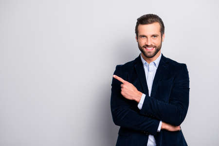 Portrait of cheerful excited joyful satisfied handsome attractive fashionable macho guy dressed in formal outfit dark velvet pointing on empty blank copyspace isolated on gray background copy-space 写真素材