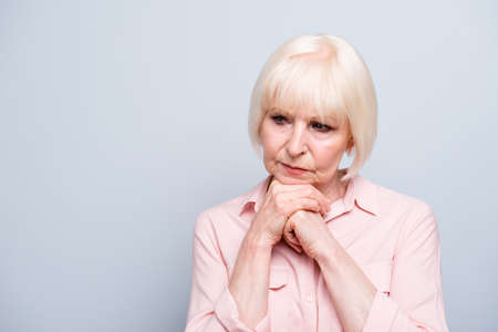 Portrait of old adult blonde caucasian sad depressed lady holding hands under chin, thinking over grey background, isolated