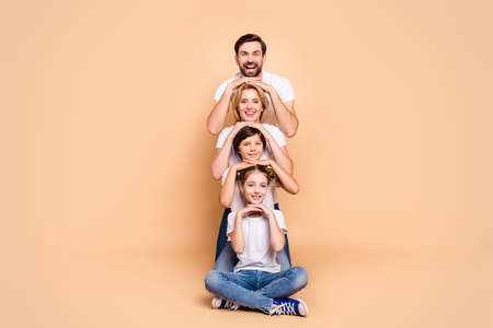 Young adorable attractive beautiful smiling family, bearded father, blonde mother, boy and girl wearing blue jeans and white T-shirts, standing in odrer of hierarchy, holding hands on each other