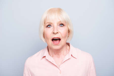 Old lady amazed shocked wow facial expression on grey background