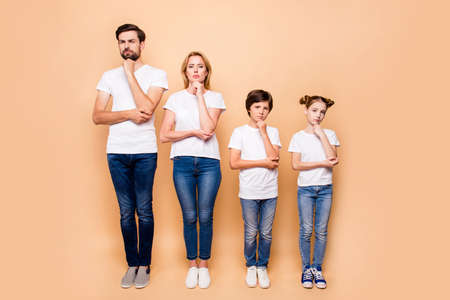 Full length portrait of beautiful family bieng confused, bearded father, blonde mother and their children wearing jeans and T-shirts, standing straight showing uncertain gesture their hands to chins Stock Photo