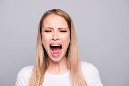 Portrait of young blonde attractive caucasian girl overreacting screaming loudly crying. Isolated over grey background