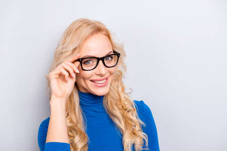 Portrait of pretty, trendy, charming,  nice, sexy, cute woman isolated on grey background looking at camera holding eyelet of glasses on her face with fingers Stock Photo
