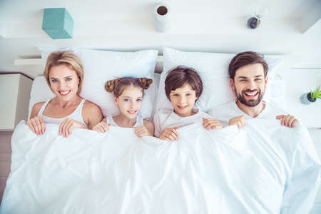 Young happy smiling family four persons lying together in bed laughing covered with blanket bedsheets. Top above high angle view Imagens