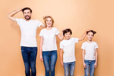 Retrato de una hermosa familia joven, padre barbudo, madre rubia y sus hijos pequeños con jeans y camisetas blancas, de pie en orden de jerarquía, colocando las manos de las cabezas de los demás