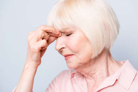 Close up portrait of old adult caucasian lady feeling head ache, pain, high blood pressure facial expression, fingers to face, on grey background, isolated Stock Photo