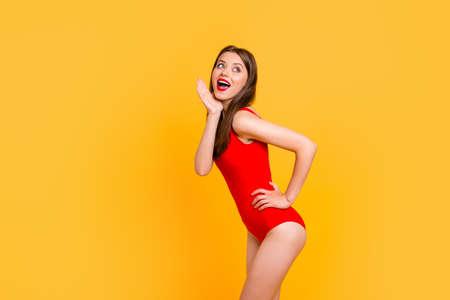 Geschokt jong meisje in een rood zwempak en een status in profiel met een brede glimlach die op gele achtergrond wordt geïsoleerd