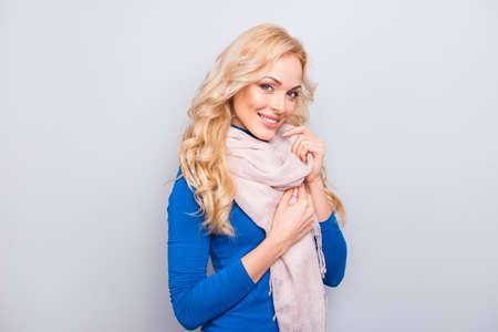 Portrait with copy space, empty place of pretty, trendy, charming, sexy,  cute, cheerful woman in blue roll-neck holding hands on scarf around neck, looking at camera, isolated on grey background Stock Photo