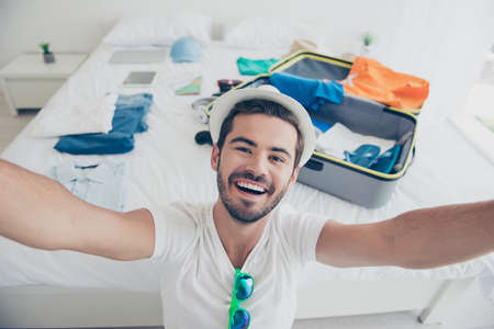 Self portrait of young attractive handsome bearded smiling brunet man in sunhat, packing stuff to a trip to bag suit at home, folded clothes. White interior room