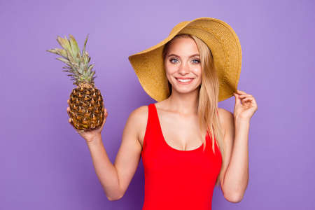 Close up portrait of beautiful and kind girl holds a pineapple in her hand and looks into the camera holding her hat by hand isolated on violet background Banco de Imagens