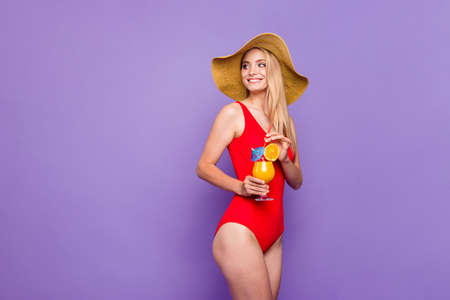 Charming and cute blonde girl standing half a turn in hat and red swimsuit laughing and looking away hold cold summer cocktail in hand isolated on bright purple background Stock Photo