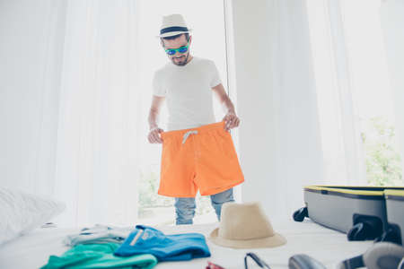 Young man trying on orange shorts before going to go on a long-awaited vacation