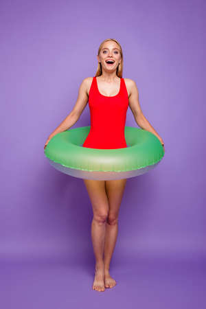 Finally, long-awaited sea! Full-size portrait of blond girls with green life buoy at the waist look enthusiastically forward isolated on purple background 免版税图像