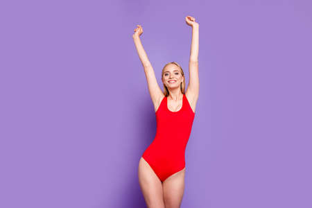 Young attractive nice gorgeous blonde smiling girl with straight hair wearing full red swimsuit, raising hands up, relaxed, having rest on vacation. Isolated over violet background