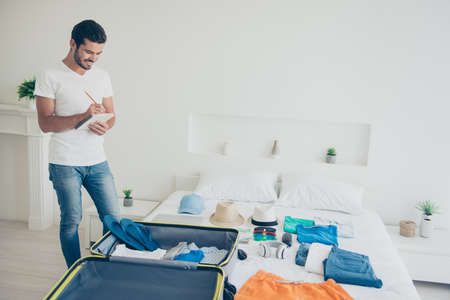 Young attractive handsome bearded smiling brunet man packing stuff to a trip, check list. White interior room Stock Photo