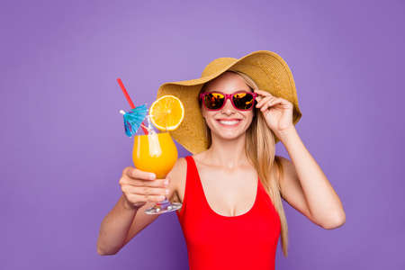 Party mood and beach style isolated on bright purple background! Blonde girl in red swimsuit laughs and offers summer cocktail for you Foto de archivo - 106203064