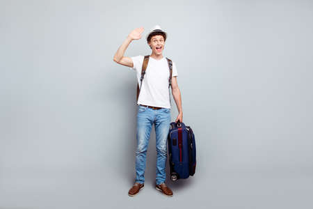 Hey, I returned from vacation! Full-size portrait of guy with a suitcase and a backpack, who waving his hand and look at the camera isolated on light gray background 写真素材