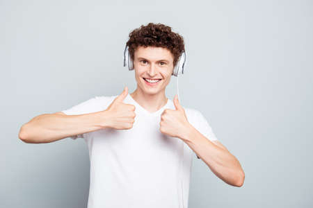 Portrait of brunet guy in big white headphones shows thumbs up isolated on light gray background