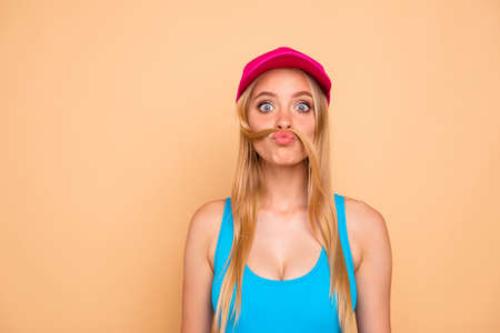 Portrait of young attractive nice cute straight-haired blonde funky girl wearing casual, bright pink cap, grimacing with curl like fake mustache. Isolated over beige background