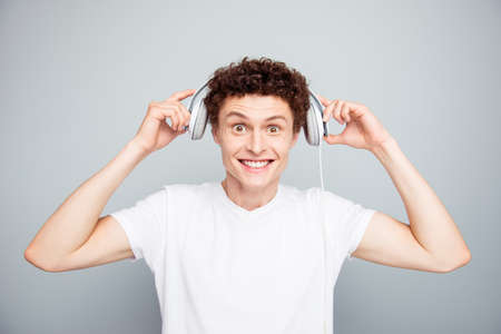 Portrait of young handsome and attractive guy dresses white headphones on his head that you listen to good music isolated on light gray background Stock Photo