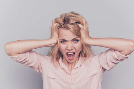 Young lovely blonde caucasian curly-haired nice pretty stressed woman yelling screaming crying. Isolated over grey background