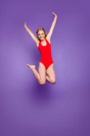 Celebrate yes hooray yeah win winner person concept. Vertical full body length size photo portrait of beautiful cheerful funny girl diving from bungee springboard isolated purple violet background