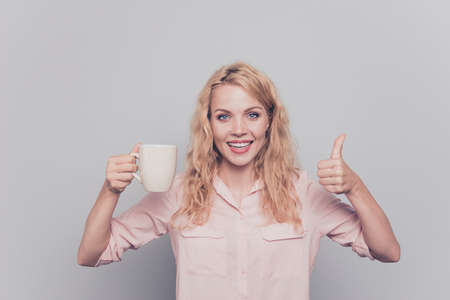 Attractive and cheerful young girl holding white mug in her hand and showing thumbs up smiling and looking at the camera isolated on gray background 版權商用圖片 - 106587925