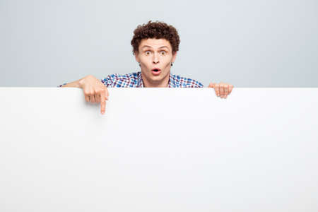 Cheerful young man standing behind the white blank banner and pointing down at a white copyspace isolated on light gray background